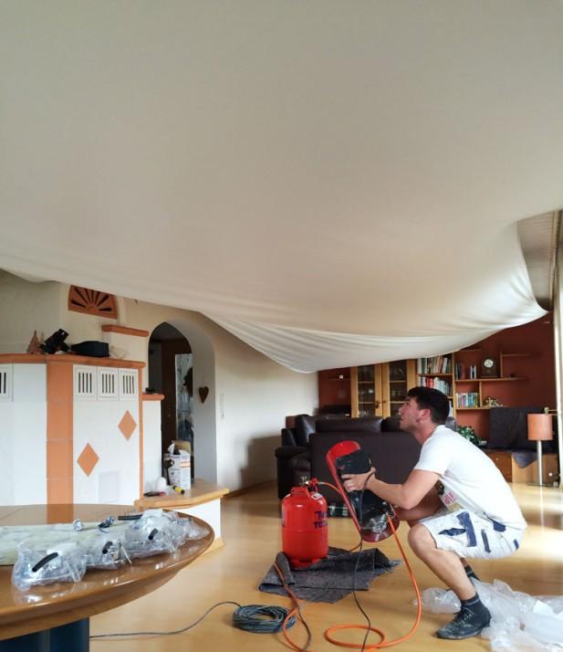 Malermeister bringt Spanndecke in Wohnzimmer an